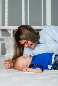 Mom plays with a baby boy on a white bed