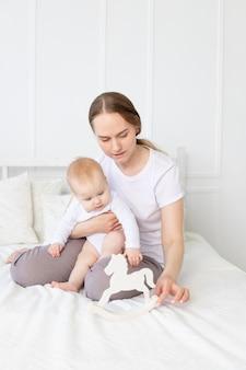 엄마는 집에서 침대에 아기 나무 장난감 말과 함께 재생, 행복한 가족