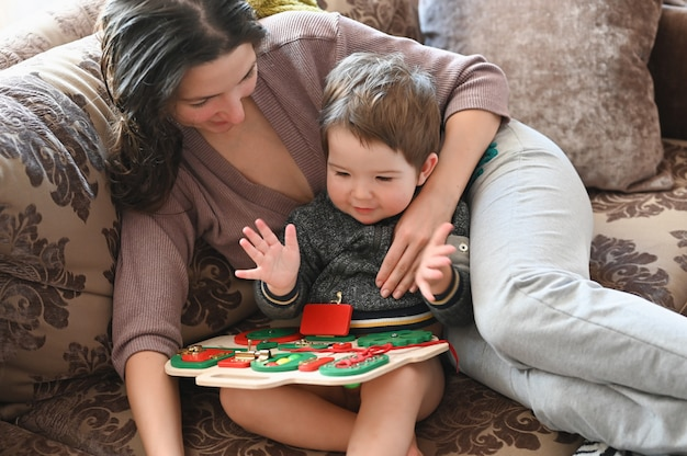Mom plays with a child on a development board. child development.