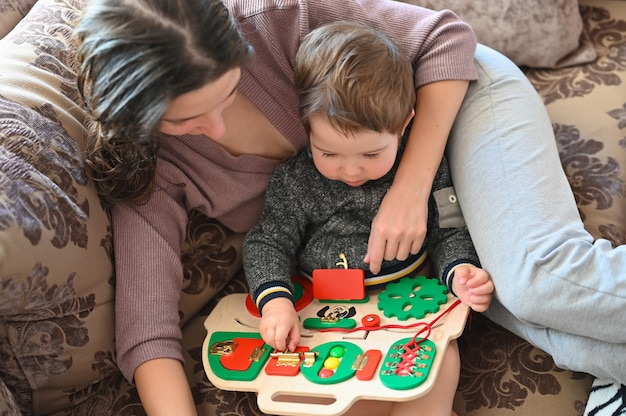 Mom plays with a child on a development board