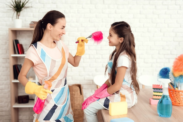 Mom plays with her daughter after cleaning the house