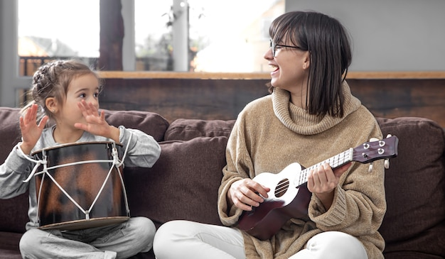 엄마는 집에서 딸과 함께 재생합니다. 악기에 대한 수업. 어린이의 발달과 가족 가치. 아이들의 우정과 가족의 개념.