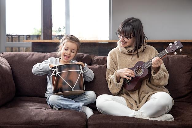 Мама играет с дочерью дома. уроки игры на музыкальном инструменте. развитие детей и семейные ценности. концепция детской дружбы и семьи.