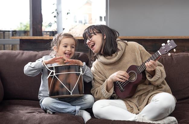 ママは家で娘と遊んでいます。楽器のレッスン。子供の発達と家族の価値観。子供の友情と家族の概念。
