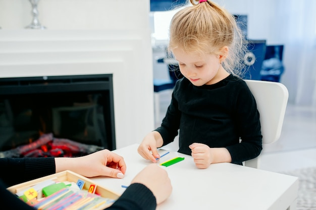 Mom plays with her daughter at the table with multi-colored wooden chopsticks, getting ready for school playing, learning the score