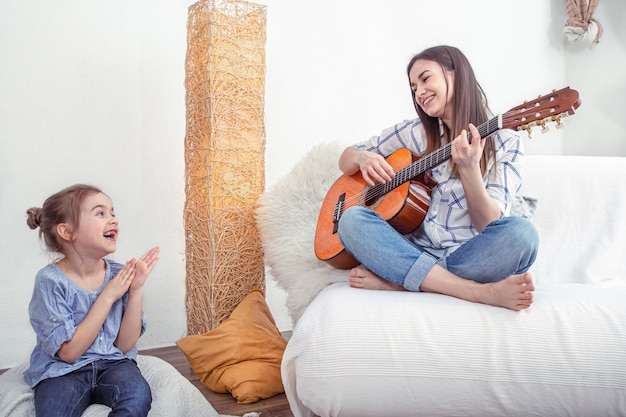 Mom plays with her daughters at home. lessons on musical instrument