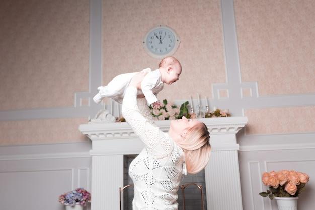 엄마는 아늑한 거실에서 아기와 놀고 있습니다. 복사 공간이 있는 사진