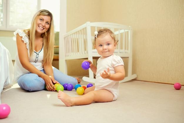 엄마는 실내에서 아기와 놀아요.