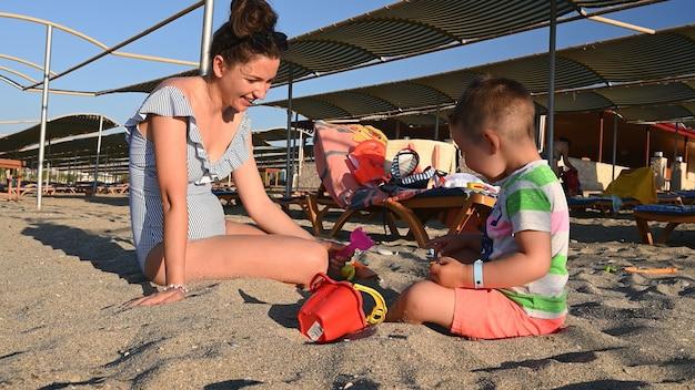 ママは海の近くで休暇中に子供と遊ぶ