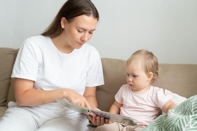 Мама показывает любопытному ребенку в книге, сидя на диване в гостиной при естественном освещении