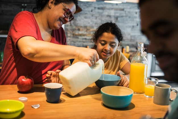 Mom pouring milk in daughter's cereal