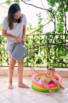 엄마는 풍선 수영장에서 어린 소녀 물을 깡통에서 붓는다