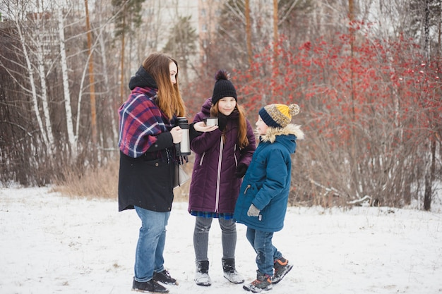 Mom pours hot tea or drink from thermos for her daughter and son, winter walk, winter