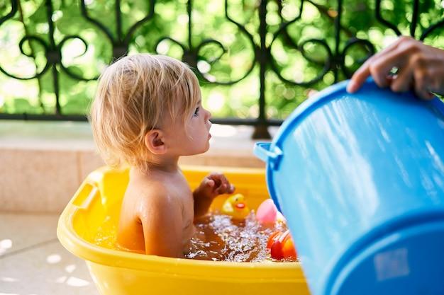 엄마는 어린 아이가 앉아 있는 대야에 양동이에서 물을 붓습니다