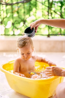 엄마는 그릇에 앉아 있는 아이에게 국자에서 물을 붓는다