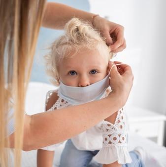 Mamma che indossa la mascherina medica sul bambino