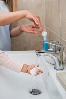 洗うために子供の手に石鹸を置くお母さん