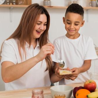 Мама кладет мед на кусочек хлеба своего сына