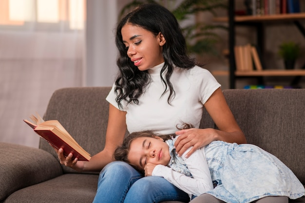 Mom reading bed story for daughter
