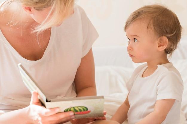 침대에서 아기를 읽는 엄마