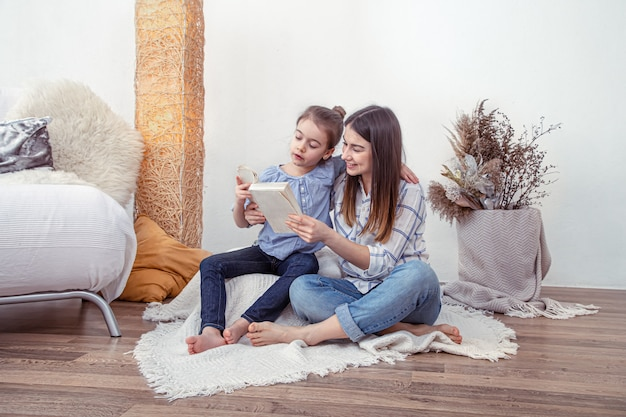 ママは家で娘と一緒に本を読みます。