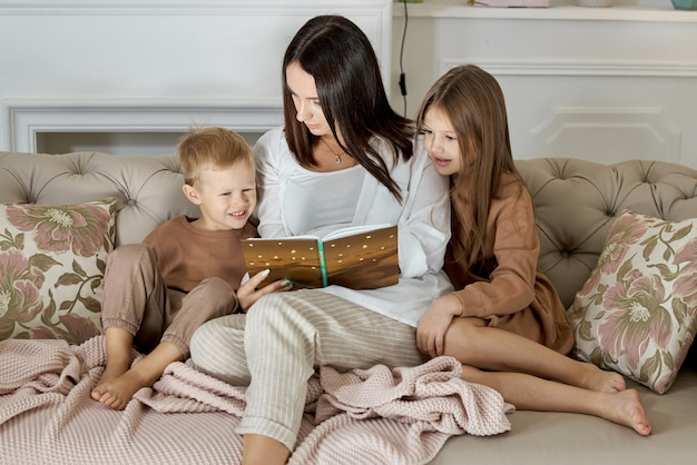 Mom reads a book to the children. a woman tells a story to a boy and a girl before going to bed. mom daughter and son relax at home on a day off