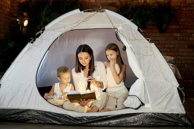 Мама читает детям сказку на ночь, сидя в палатке дома. мать, сын и дочь обнимаются и читают книгу с фонариком в руках