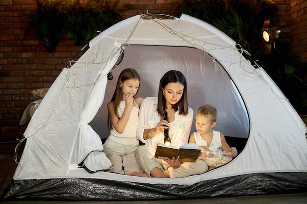 Мама читает детям сказку на ночь, сидя в палатке дома.