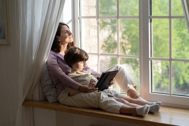 デジタルタブレットで遊んでいる子供を抱き締める窓辺に座って週末に小さな息子とリラックスしたお母さん