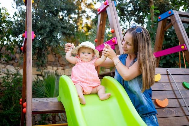 엄마는 여름에 집 마당에서 놀이터에서 미끄럼틀 아래로 여자 아기를 굴려 즐겁게 놀고 있다