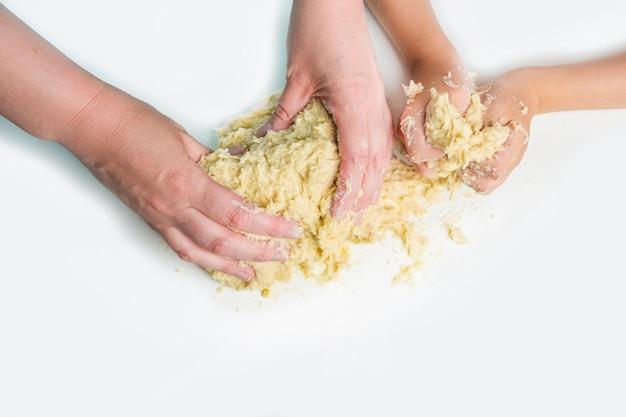 Рука мамы и ребенка замешивает тесто. приготовление теста для выпечки в домашней кухне. навыки дошкольника, маленький помощник.