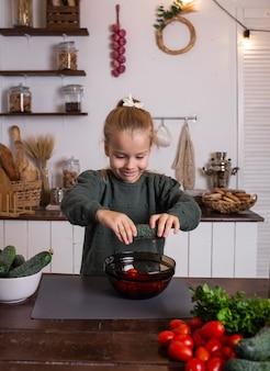 식탁에서 샐러드를 요리하는 법을 배우는 엄마의 조수