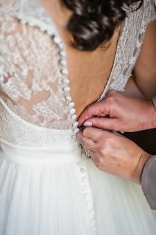 Руки мамы завязывают платье невесты