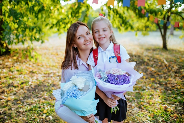 Mom sees off to school a little cute daughter with bouquets of flowers