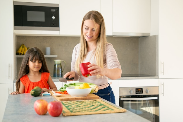 Mom showing daughter how to cook salad for dinner. girl and her mother cutting vegs on kitchen counter. medium shot, copy space. family cooking concept