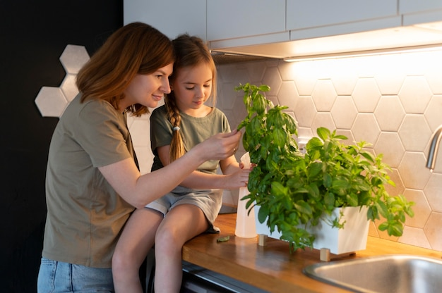 그녀의 딸에게 식물을 돌보는 방법을 보여주는 엄마