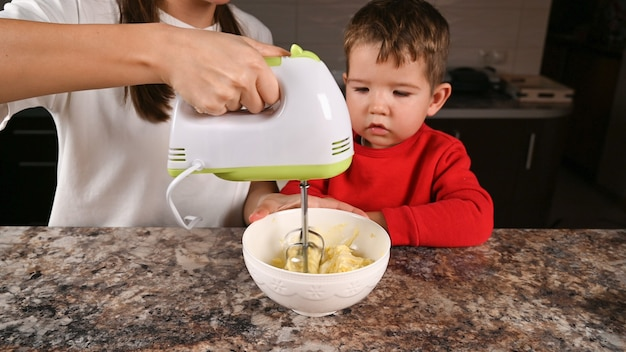 Mom shows the child how to work with a mixer