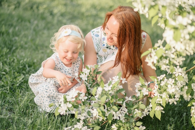 Mom shows little daughter apple blossoms. high quality photo