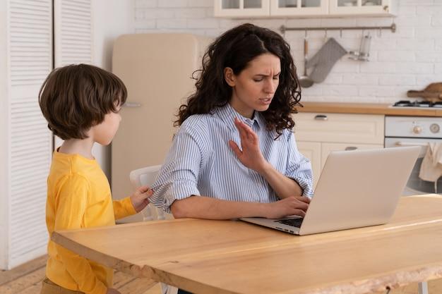 ママはラップトップで作業中の封鎖中にホームオフィスのテーブルのそばに座っています。子供は気を散らして音を立てる