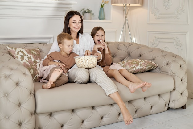 Mom sits on the couch with her son and daughter and watch a movie. a woman, a boy and a girl eat popcorn while watching a movie. the family is resting at home on the weekend