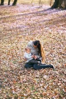 Mom sits on fallen leaves in the park and holds a baby with a rattle on her lap bending over him
