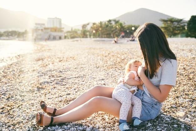 ママは小石のビーチに座って、海のそばで小さな女の子に授乳します