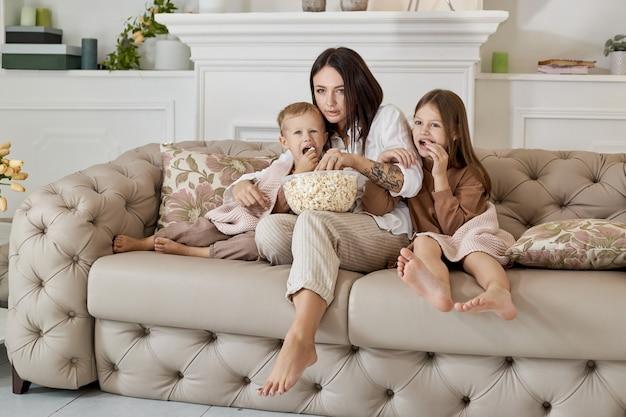 ママは息子と娘と一緒にソファに座って映画を見ます。映画を見ながら、女性、男の子、女の子がポップコーンを食べます。家族は週末に家で休んでいます