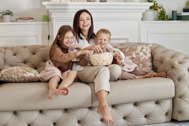 Мама сидит на диване с сыном и дочкой и смотрит фильм