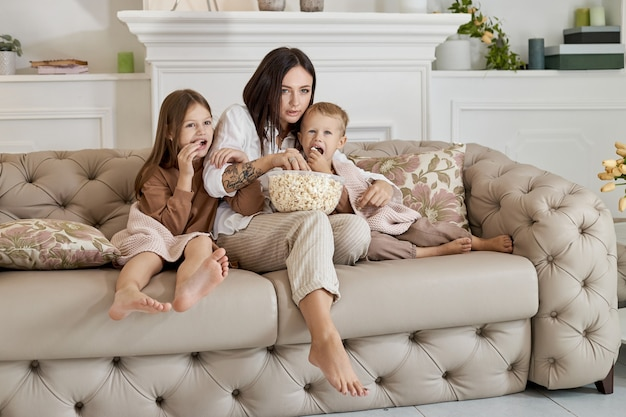 ママは息子と娘と一緒にソファに座って映画を見る