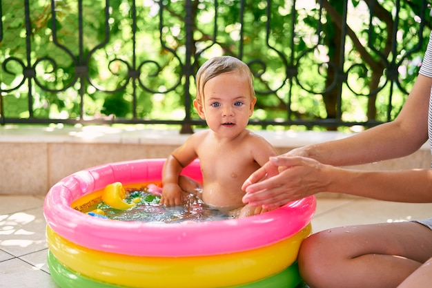 엄마는 작은 풍선 수영장에서 어린 아이 옆에 바닥에 앉는다