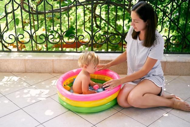 엄마는 풍선 수영장에서 어린 소녀 옆에 타일 바닥에 앉아