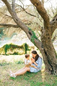 엄마는 올리브 과수원의 나무 아래 풀밭에 무릎을 꿇고 어린 아들과 함께 앉아 놀고 있습니다.