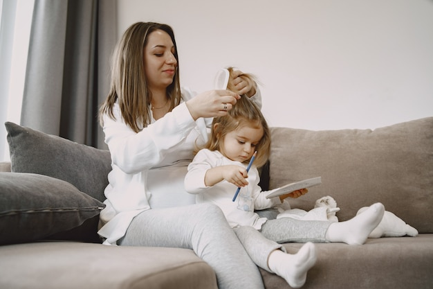 Mom sitting on a couch ties her daughter's hair.