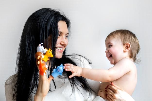ママは笑顔で、健康で小さな笑顔の子供と指で動物のゲームをする